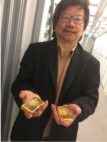 Khoo holding bars of gold