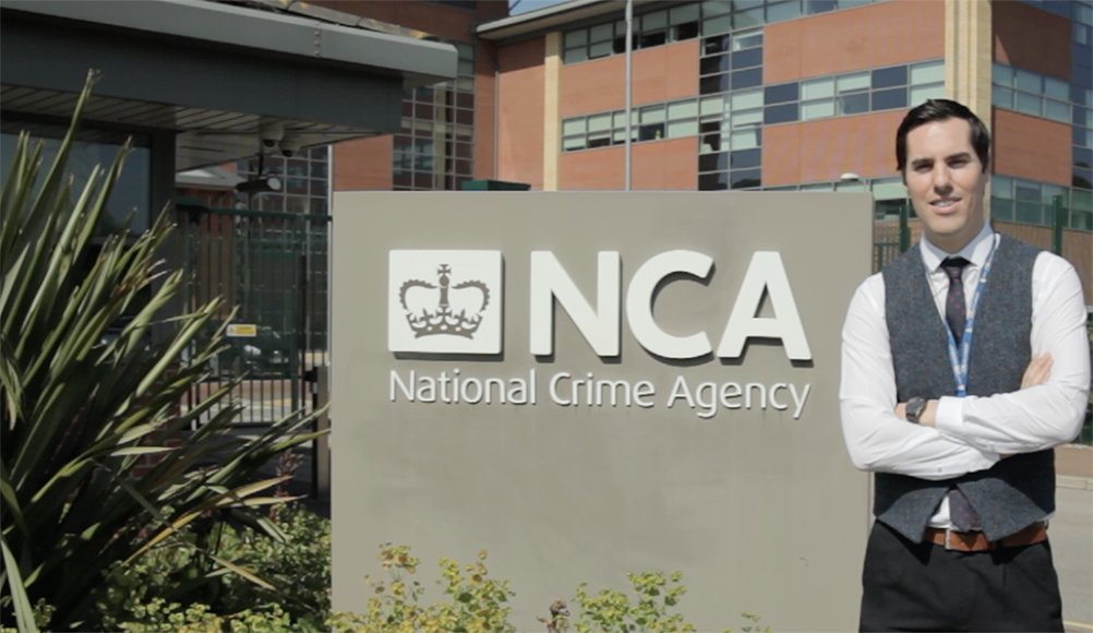 Man stood by the NCA sign outside NCA HQ